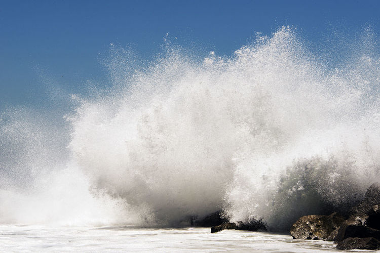 Waves Splashing In Sea Against Clear Sky During Sunny Day