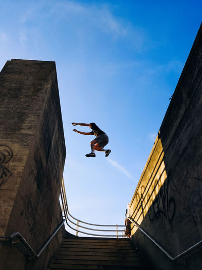 Low angle view of man jumping above steps against blue sky