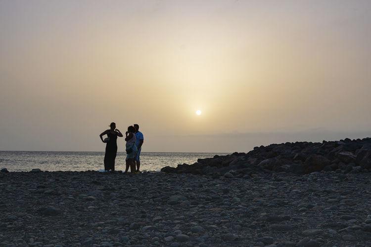 Men standing on beach against sky during sunset