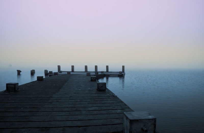 Wooden jetty in sea against clear sky