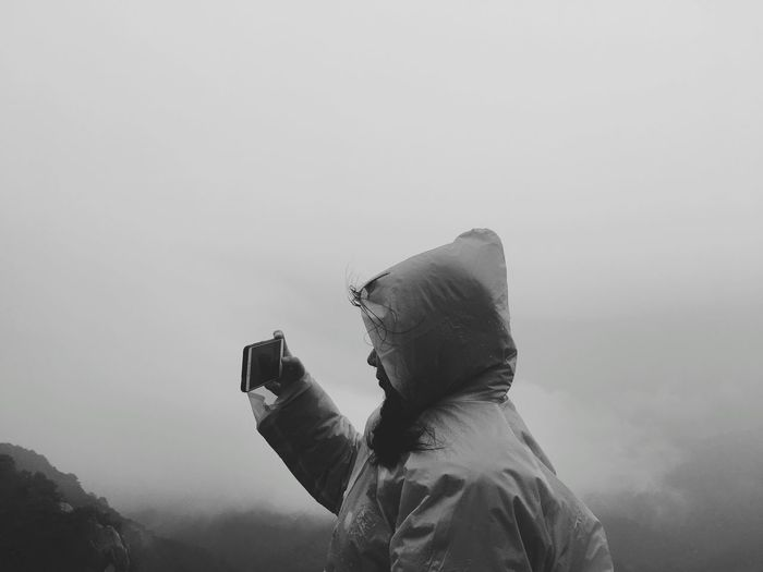 Side view of woman photographing with phone