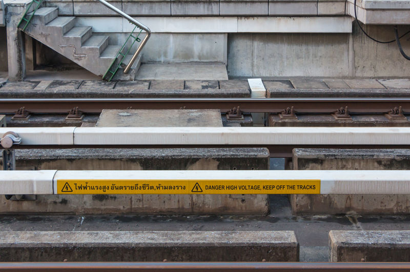 High voltage warning sign on track of sky train. Aware Awareness Beware Caution Construction Dangerous Electric Electricity  High Voltage Metal Railing Remind Safty Sign Sky Train Staircase Steps Steps And Staircases Text Track Train Voltage Wall Warning Way