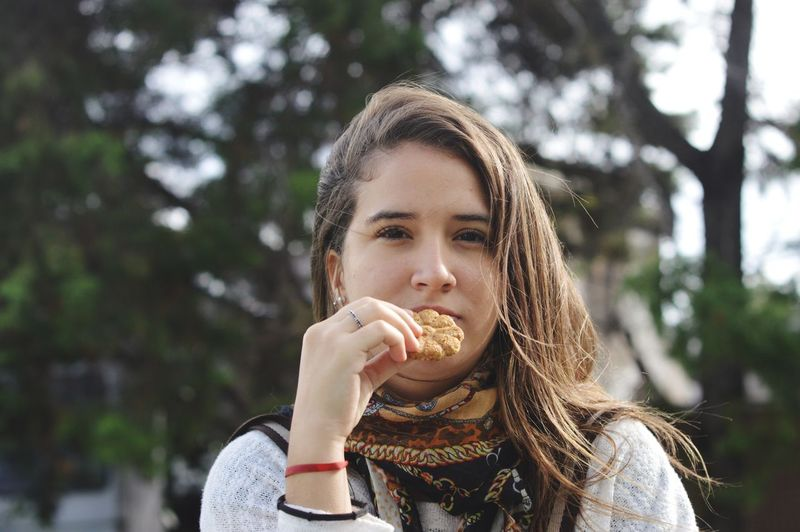 Portrait of young woman having cookie against tree
