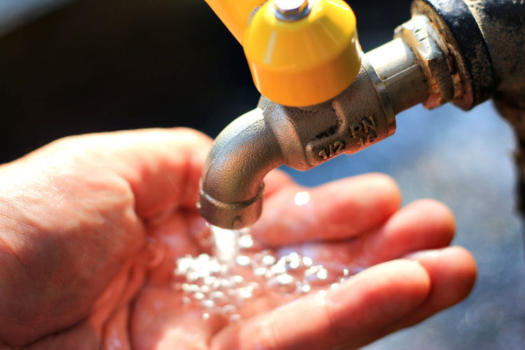 Water Flowing From Faucet On Hand Of Person
