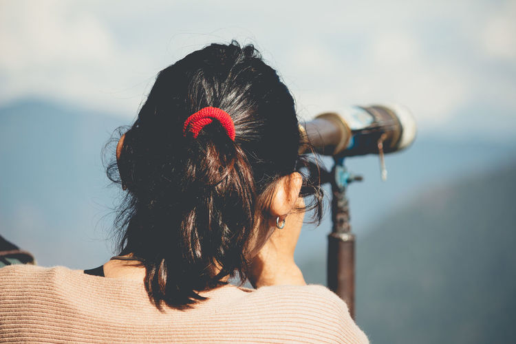 Rear view of woman looking down against sky