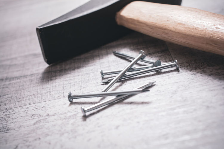 Hammer And Nails On A Table, DIY Concept Artisan Construction Copy Space Craftsman DIY Home Improvement Nails Board Close-up Concept Equipment Hammer Hardware High Angle View Macro Maintenance Repair Stainless Table Tools