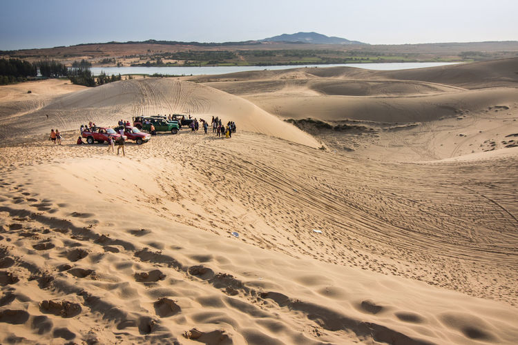Group of people with vehicles on sand dune in desert