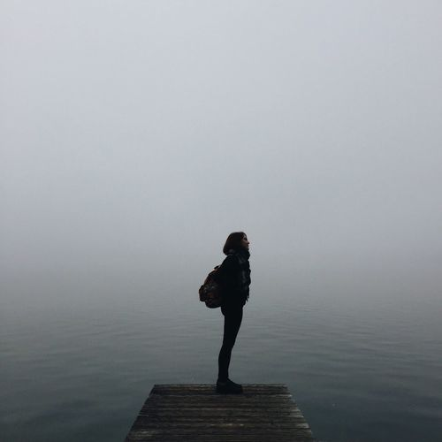 Woman Standing On Pier Over In Foggy Weather