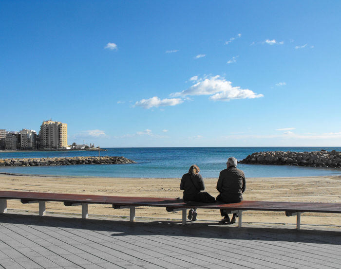 a couple by the beach Beach City Urban Skyline Water Cityscape Togetherness Sitting Sea Full Length Relaxation Beach Park Bench Promenade Park - Man Made Space Couple Friend Horizon Over Water Bench Leisure