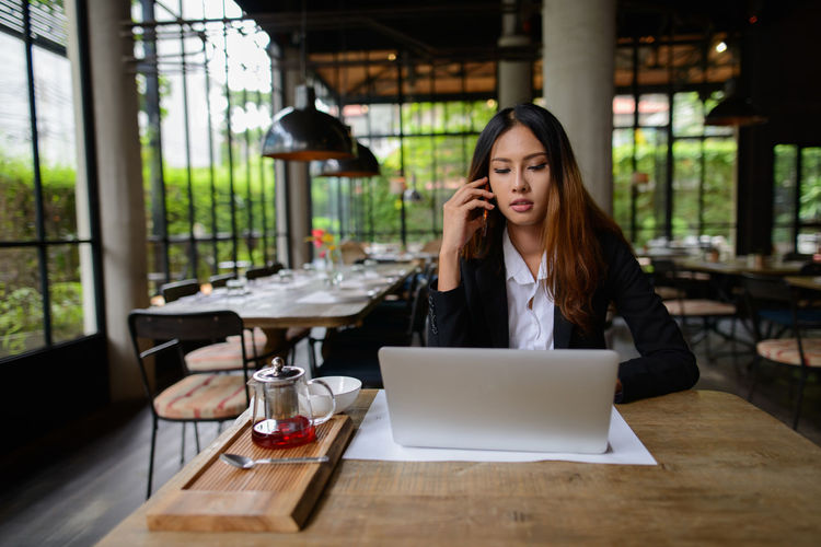 Businesswoman using laptop while sitting at restaurant
