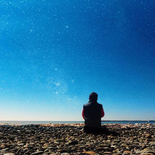 Rear view of man sitting against sea at beach