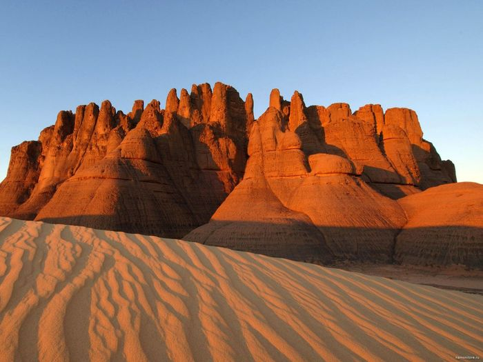 Rock formations against clear blue sky at sahara desert