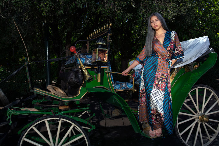 Sensuous woman standing in carriage against trees