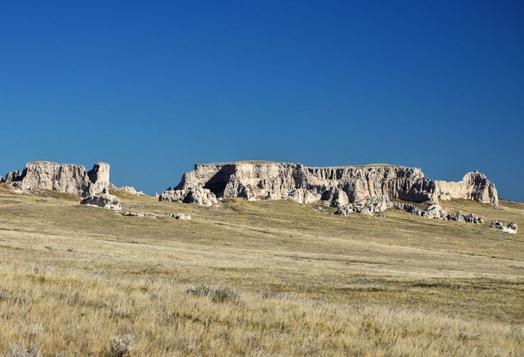 On the horizon Tall Blue Color Rural Scene Country Side Sunshine Outdoors In The Distance. Grass West Of Lusk Wyoming Shadows Pasture Rock Formations
