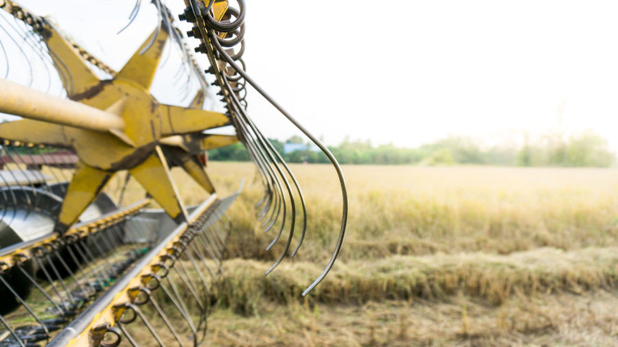 Close-up of combine harvester on field against sky
