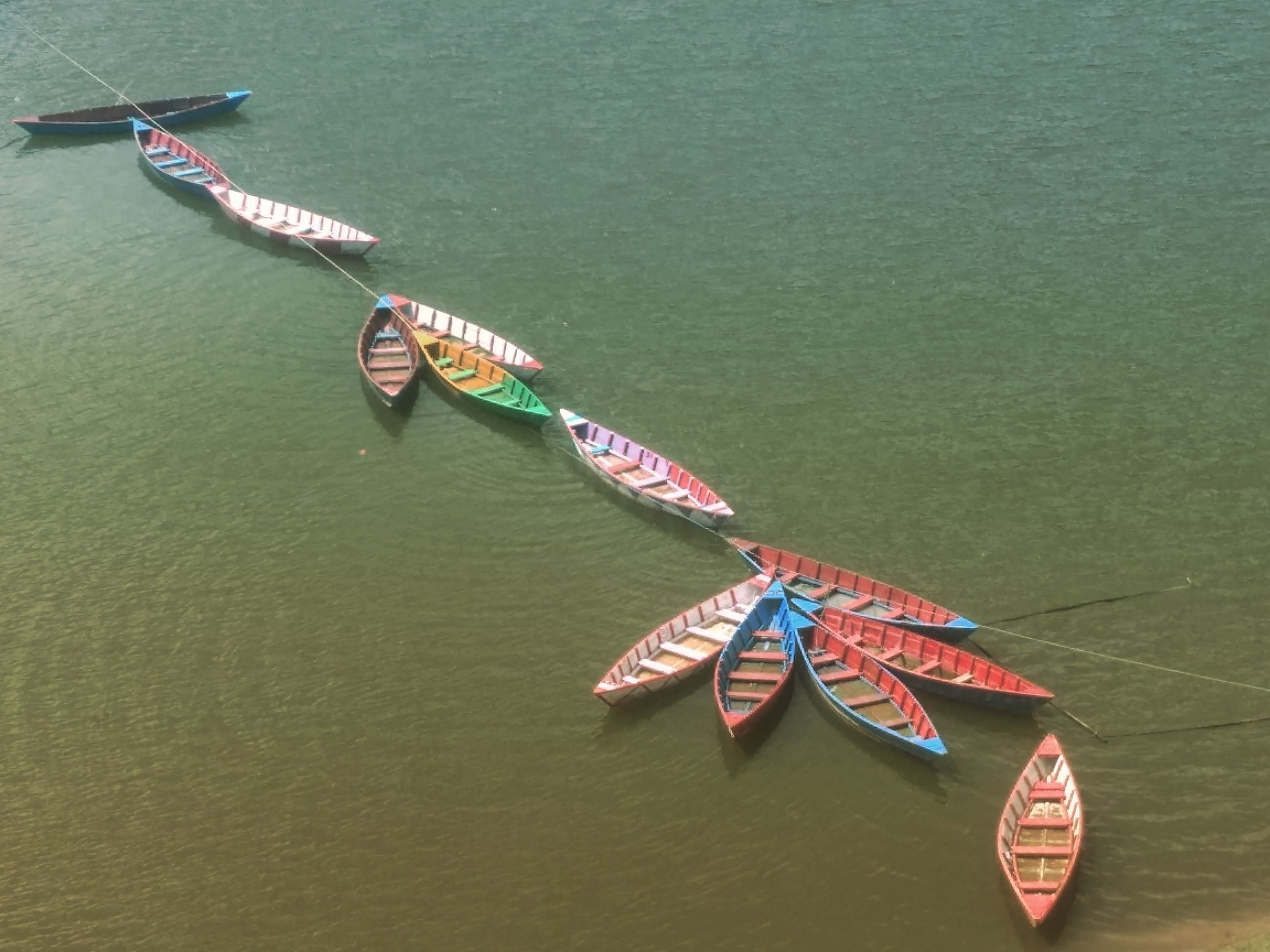 nautical vessel, transportation, mode of transport, high angle view, day, water, flag, outdoors, real people, nature, gondola - traditional boat