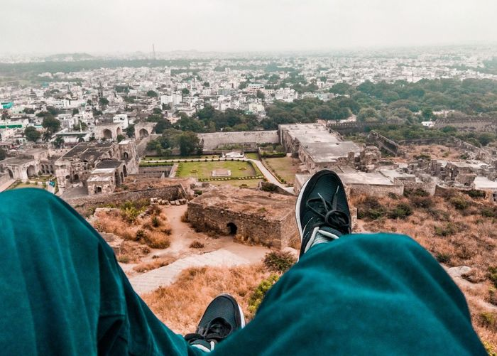 Low section of man sitting on mountain against cityscape