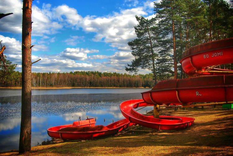 Red slide at calm lake against blue sky and clouds