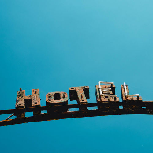 LOW ANGLE VIEW OF Old Hotel Sign AGAINST CLEAR BLUE SKY