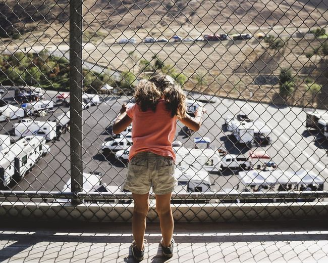 Rear view of girl standing by chainlink fence on sunny day