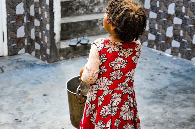 Rear view of girl holding bucket