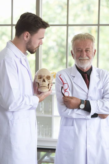 Male Doctors Examining Human Skulls In Hospital