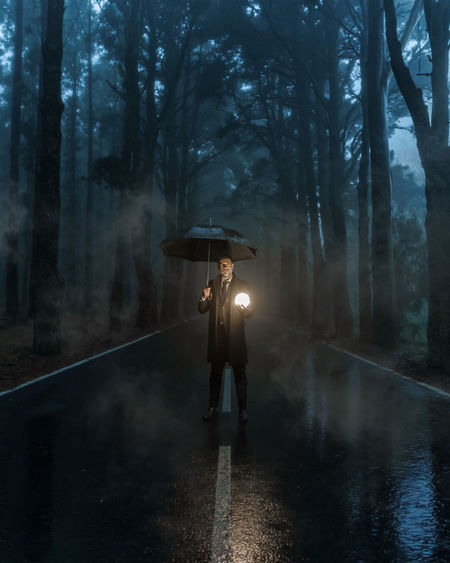 Man standing on wet road in forest during rainy season