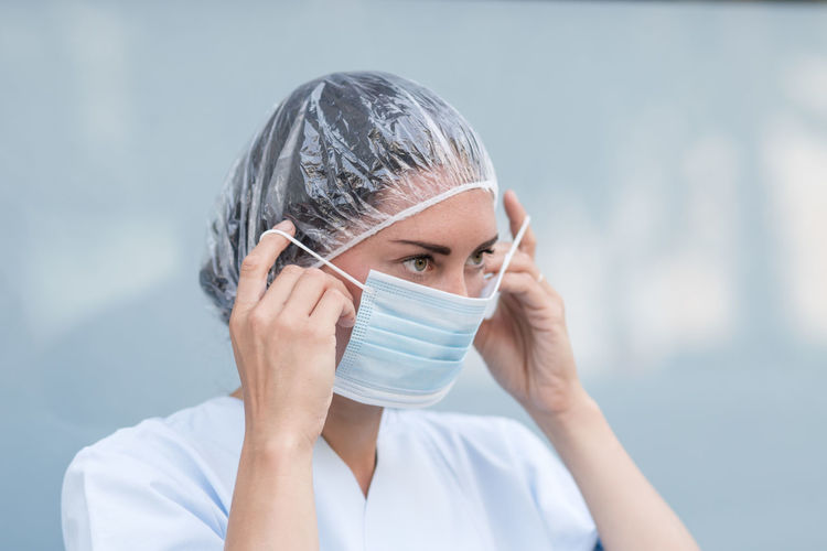 Portrait of a woman doctor putting on and fixing her surgical protective mask before her work shift