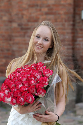 Young woman holding red flower