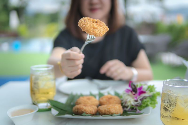 Midsection of woman eating fried chicken on table