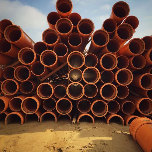 Stack of water pipes on field