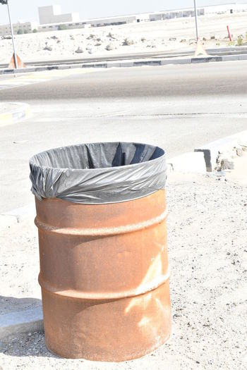 Close-up of garbage bin on street in city