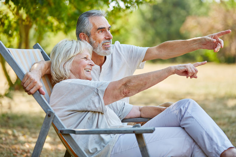 Smiling senior couple pointing while sitting at park