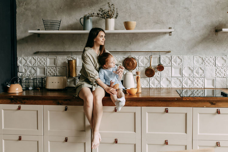 Happy mom and little daughter cooking together in the kitchen