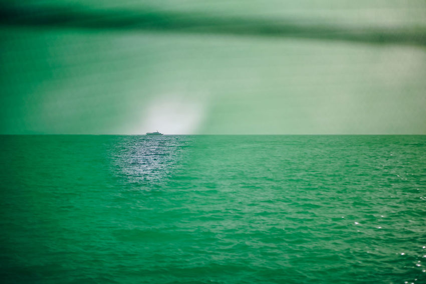 Photograph taken where a passenger boat can be seen through a tiny hole in the green net. Lonely passenger boat ASIA Ferry Passenger Transport Transportation Travel View Wave Boat Color Cruise Hole Journey Nautical Vessel Net Ocean Outdoors Sea Seascape Seen Through Ship Sky Vessel Voyage Water