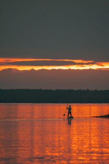 Silhouette man in sea against orange sky