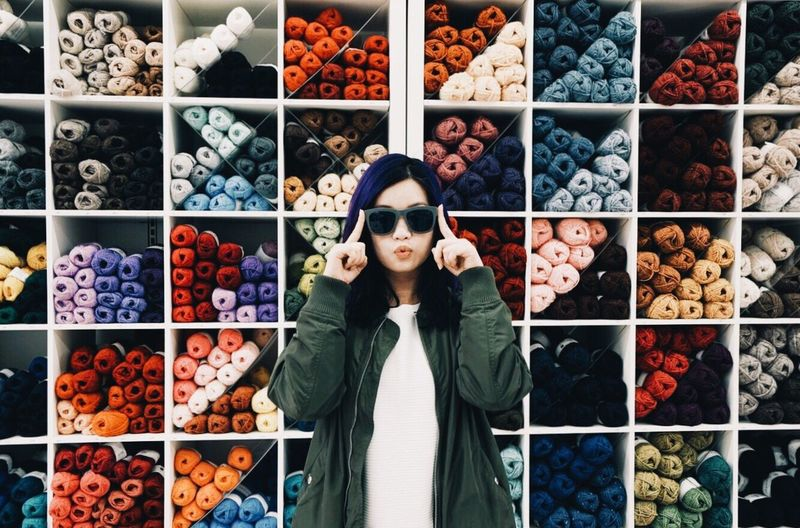 Portrait of young woman standing against colorful wool shelves at store