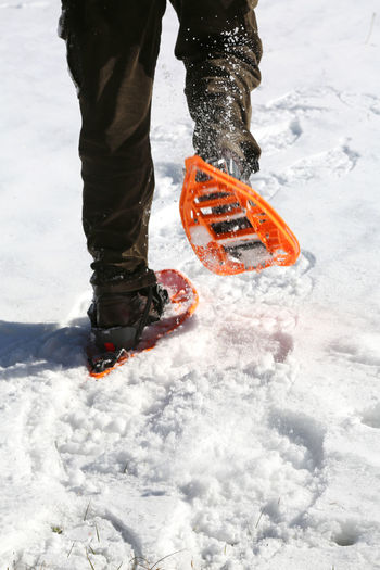 man runs with orange snowshoes in mountains on white snow Hiking Man Snowshoe Winter Wintertime Adventure Cold Cold Temperature Equipment Extreme Sports Hike Legs Mountain Snow Snow Shoeing Snow Shoes Snowshoe Trip Snowshoeing Snowshoes Sport