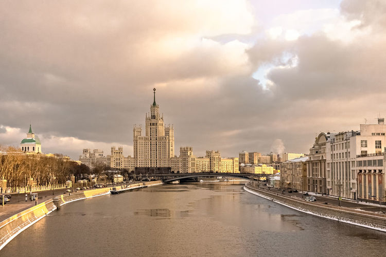 Bridge over river amidst buildings in city against cloudy sky