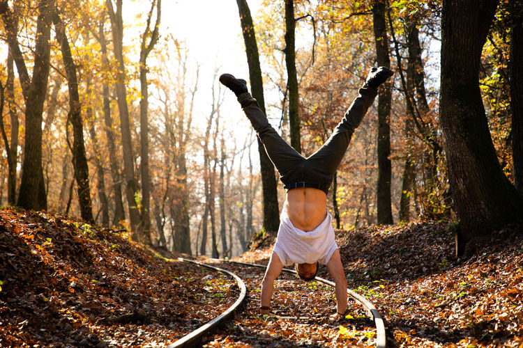 Man doing handstand on land in forest