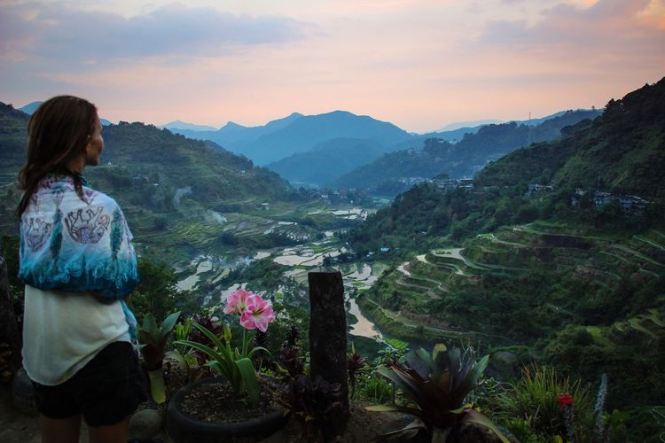Rear View Of Woman Looking At Rice Terraces Against Cloudy Sky