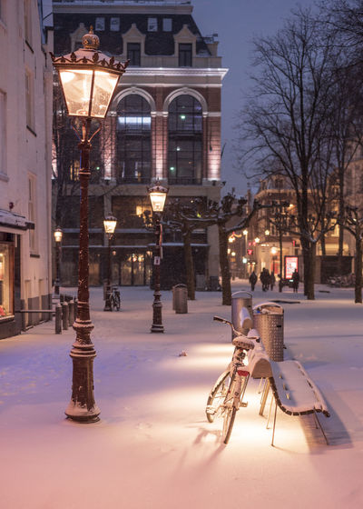 Illuminated street light and buildings in city at winter