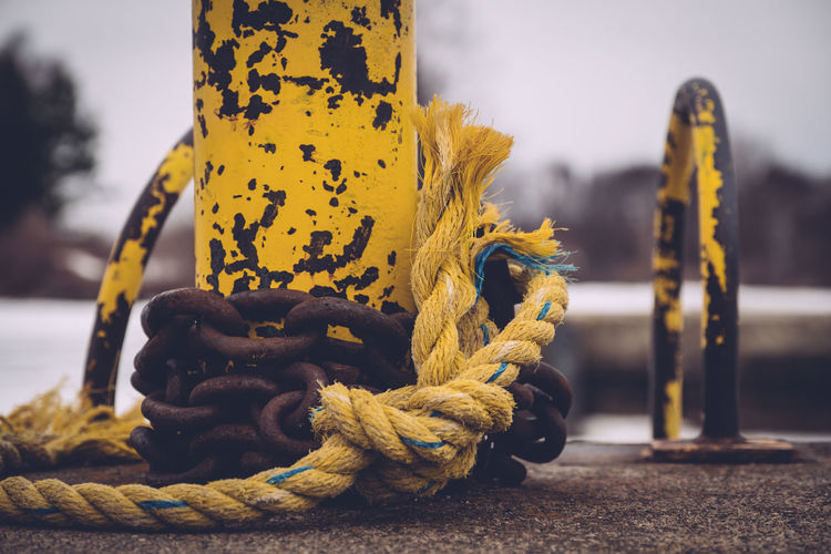 Close-up of rope and chain on bollard