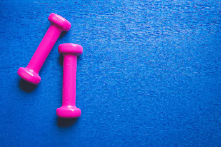 Fitness Equipment Dumbbell Blue Pink Color Indoors  No People Close-up Red Still Life Table High Angle View Vibrant Color Directly Above Plastic Weight Metal Studio Shot Copy Space Strength Weights Two Objects Blue Background