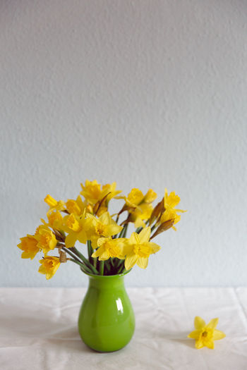 Close-up of yellow flowers in vase on table