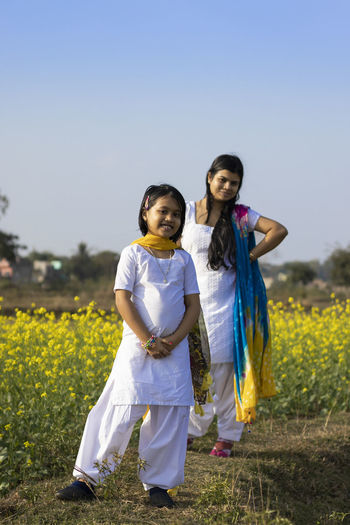 A beautiful indian woman and her daughter in white dress standing near yellow mustard flower field