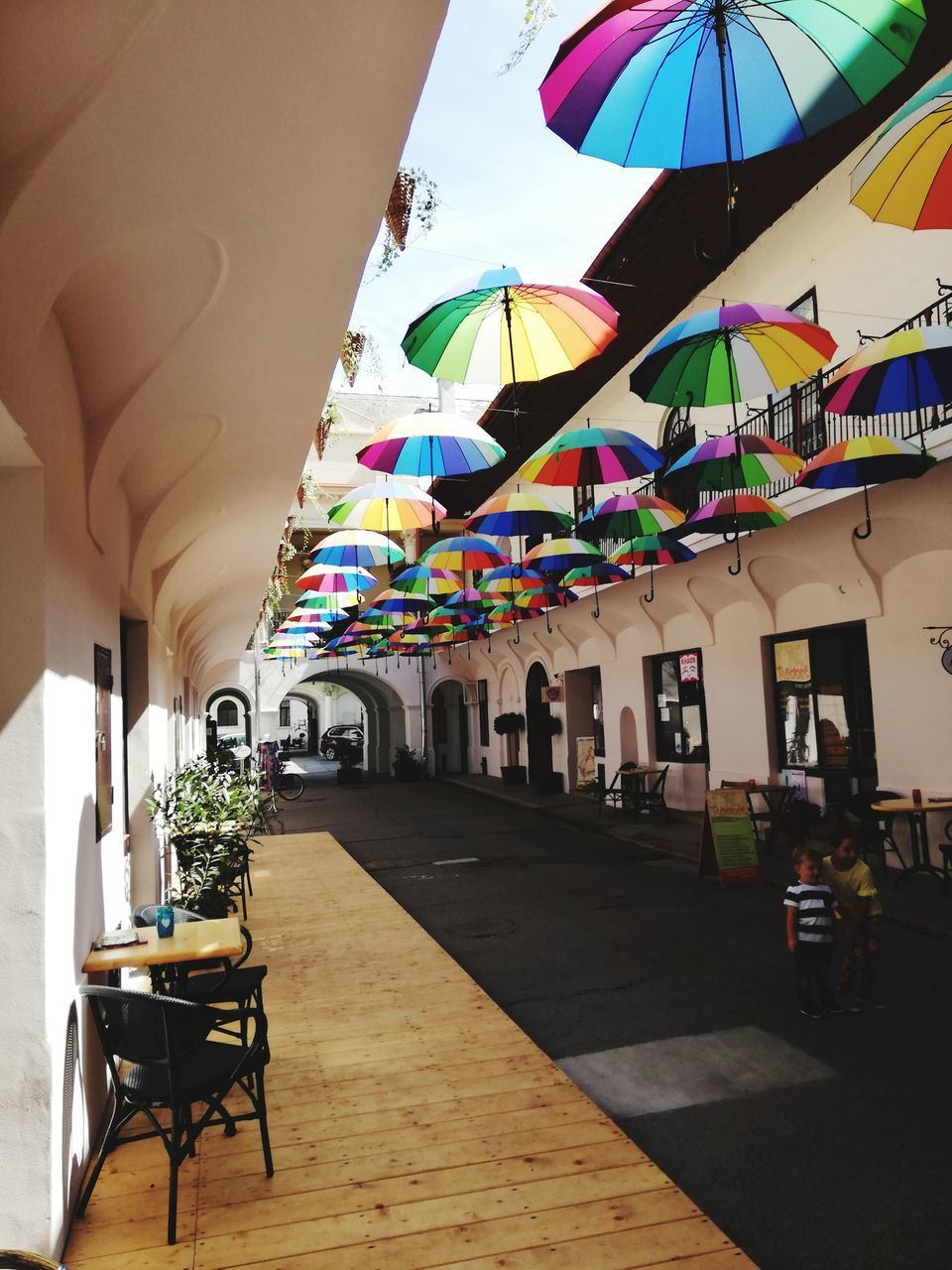 architecture, built structure, building exterior, seat, building, table, chair, restaurant, multi colored, umbrella, parasol, nature, day, business, decoration, outdoors, no people, potted plant, cafe, ceiling