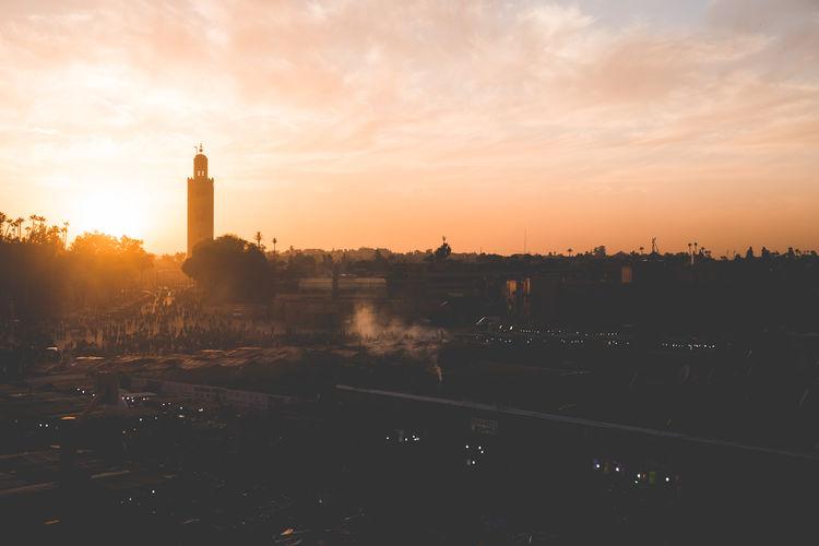 Fire on Marrakech; Jamaa El Fna, 2017 Architecture Built Structure Building Exterior Sky Sunset Tower Building Nature Cloud - Sky Orange Color No People City Guidance Sunlight Cityscape Outdoors Silhouette Travel Destinations Sun History Office Building Exterior Skyscraper