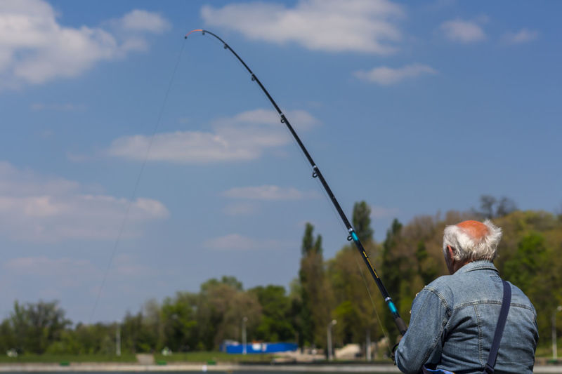 Chisinau, Moldova - April 27, 2016: Elderly man catching fish at the Valea Morilor lake in Chisinau, Moldova Catching Fish Elderly Man Fish Fisherman Fishing Fishing Rod Leisure Activity Man Man Fishing