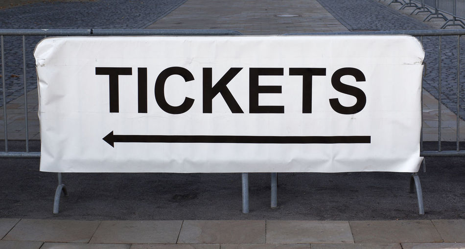 Ticket sign by railing on footpath
